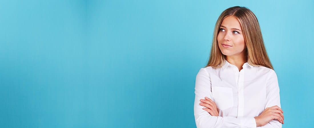 Selbstbewusste, nachdenkliche Frau vor blauem Hintergrund | Selbstbewusstsein stärken | Reset Your Head Audio-Hypnose